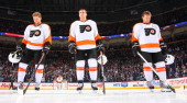 Claude Giroux Matt Read and Kimmo Timonen of the Philadelphia Flyers stand on the blueline during the singing of the National anthems prior to puck...