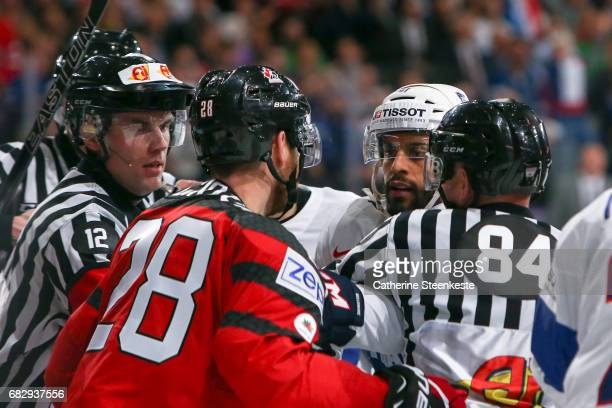 Claude Giroux of Canada fights with Pierre Edouard Bellemare of France during the 2017 IIHF Ice Hockey World Championship game between Canada and...