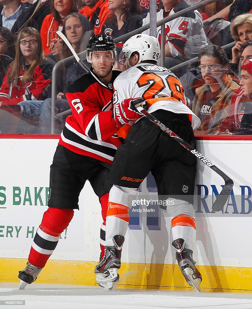 Claude Giroux #28 of the Philadelphia Flyers and Andy Greene #6 of the New Jersey Devils come together at the boards during the game at the Prudential Center on March 13, 2013 in Newark, New Jersey.