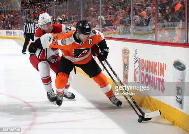 Claude Giroux of the Philadelphia Flyers battles for the puck along the boards against Brett Pesce of the Carolina Hurricanes on April 9 2017 at the...