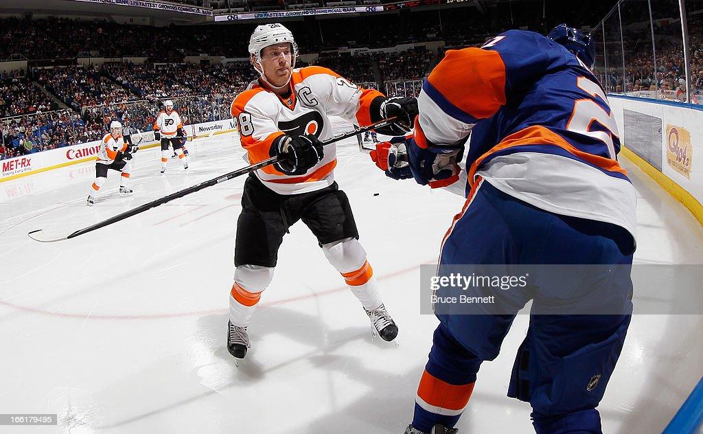 Claude Giroux #28 of the Philadelphia Flyers checks Kyle Okposo #21 of the New York Islanders at the Nassau Veterans Memorial Coliseum on April 9, 2013 in Uniondale, New York.