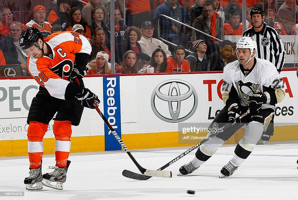 Claude Giroux #28 of the Philadelphia Flyers clears the puck in front of Craig Adams #27 of the Pittsburgh Penguins at Wells Fargo Center on January 19, 2013 in Philadelphia, Pennsylvania.