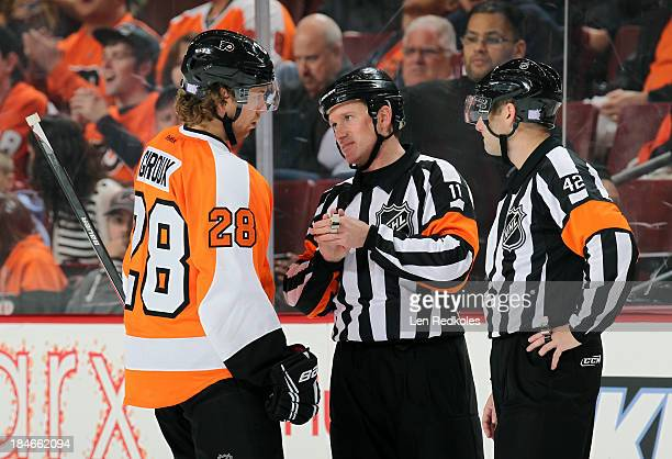 Claude Giroux of the Philadelphia Flyers discuss a call with feferees Kelly Sutherland and Darcy Burchell during NHL action against the Florida...