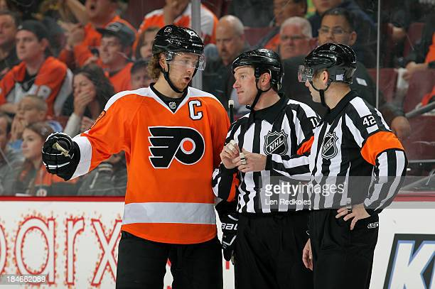 Claude Giroux of the Philadelphia Flyers discuss a call with referees Kelly Sutherland and Darcy Burchell in NHL action against the Florida Panthers...