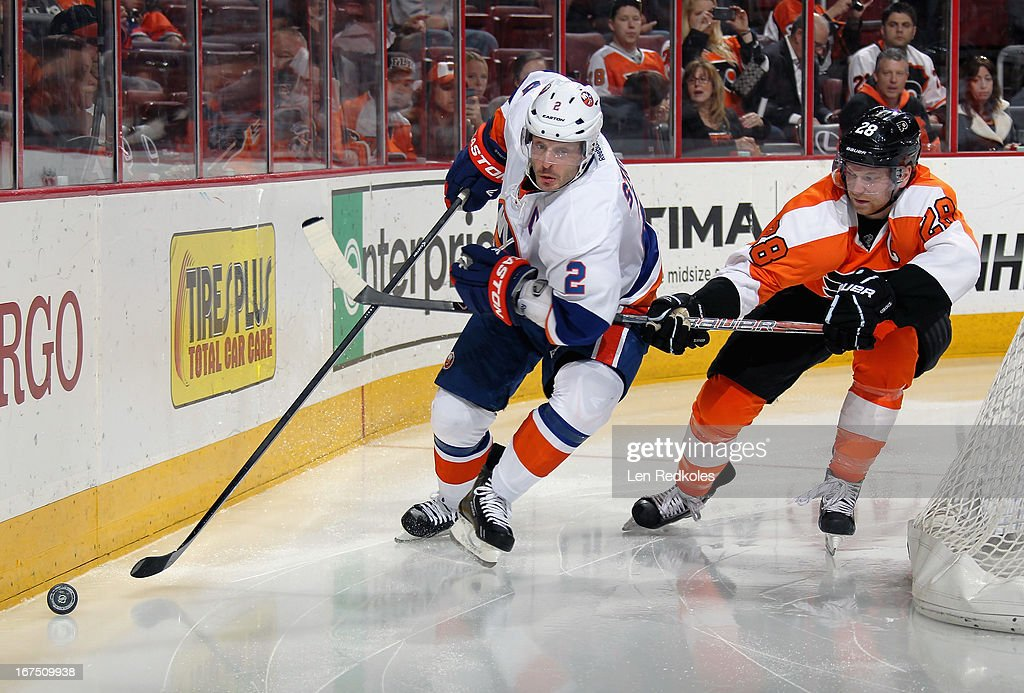 <a gi-track='captionPersonalityLinkClicked' href=/galleries/search?phrase=Claude+Giroux&family=editorial&specificpeople=537961 ng-click='$event.stopPropagation()'>Claude Giroux</a> #28 of the Philadelphia Flyers hooks <a gi-track='captionPersonalityLinkClicked' href=/galleries/search?phrase=Mark+Streit&family=editorial&specificpeople=636976 ng-click='$event.stopPropagation()'>Mark Streit</a> #2 of the New York Islanders as Streit skates with the puck behind the net on April 25, 2013 at the Wells Fargo Center in Philadelphia, Pennsylvania.