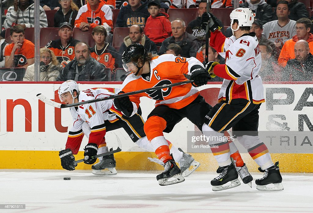 Claude Giroux #28 of the Philadelphia Flyers in action against Mikael Backlund #11 and Dennis Wideman #6 of the Calgary Flames on February 8, 2014 at the Wells Fargo Center in Philadelphia, Pennsylvania.