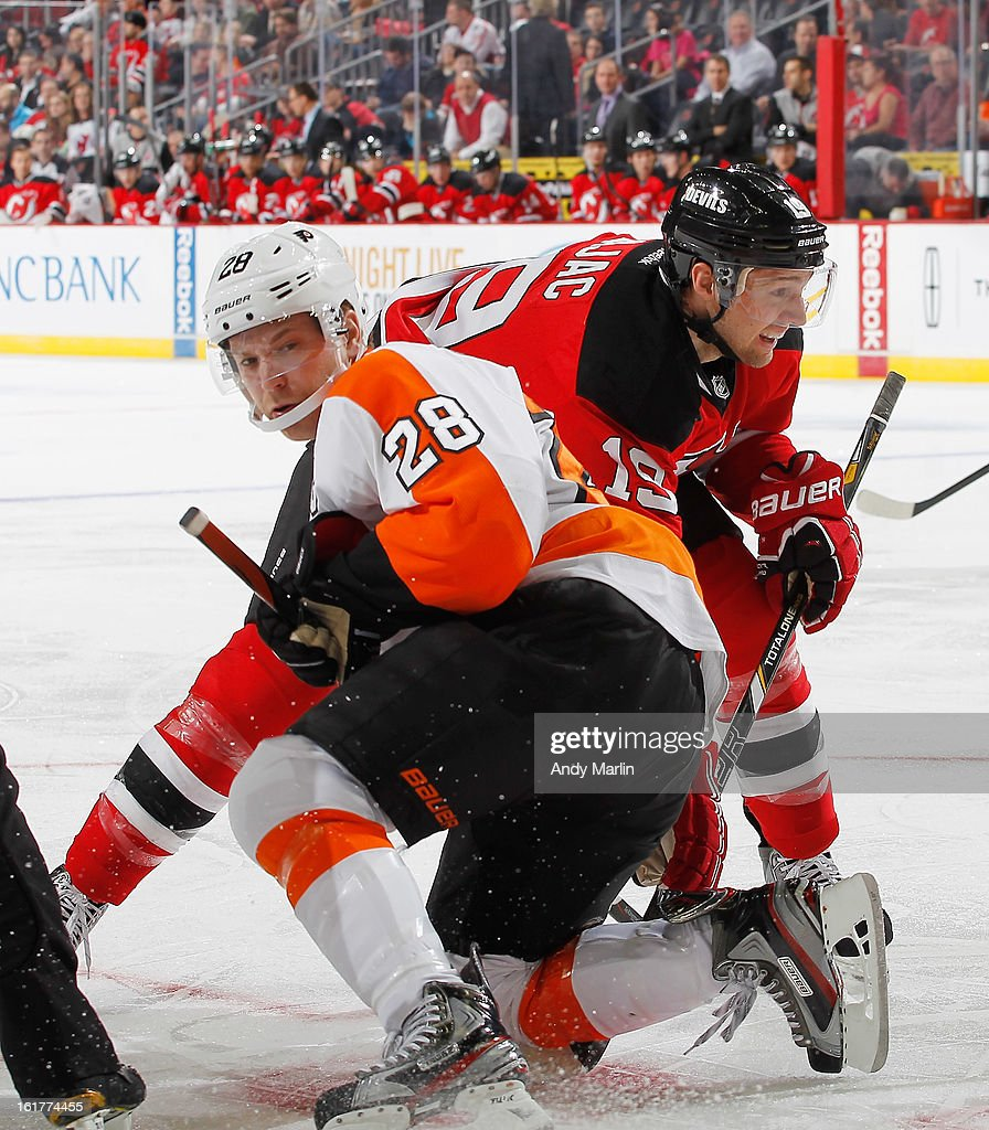 Claude Giroux #28 of the Philadelphia Flyers playing in his 300th NHL game and Travis Zajac #19 of the New Jersey Devils battle for position after a faceoff during the game at the Prudential Center on February 15, 2013 in Newark, New Jersey.