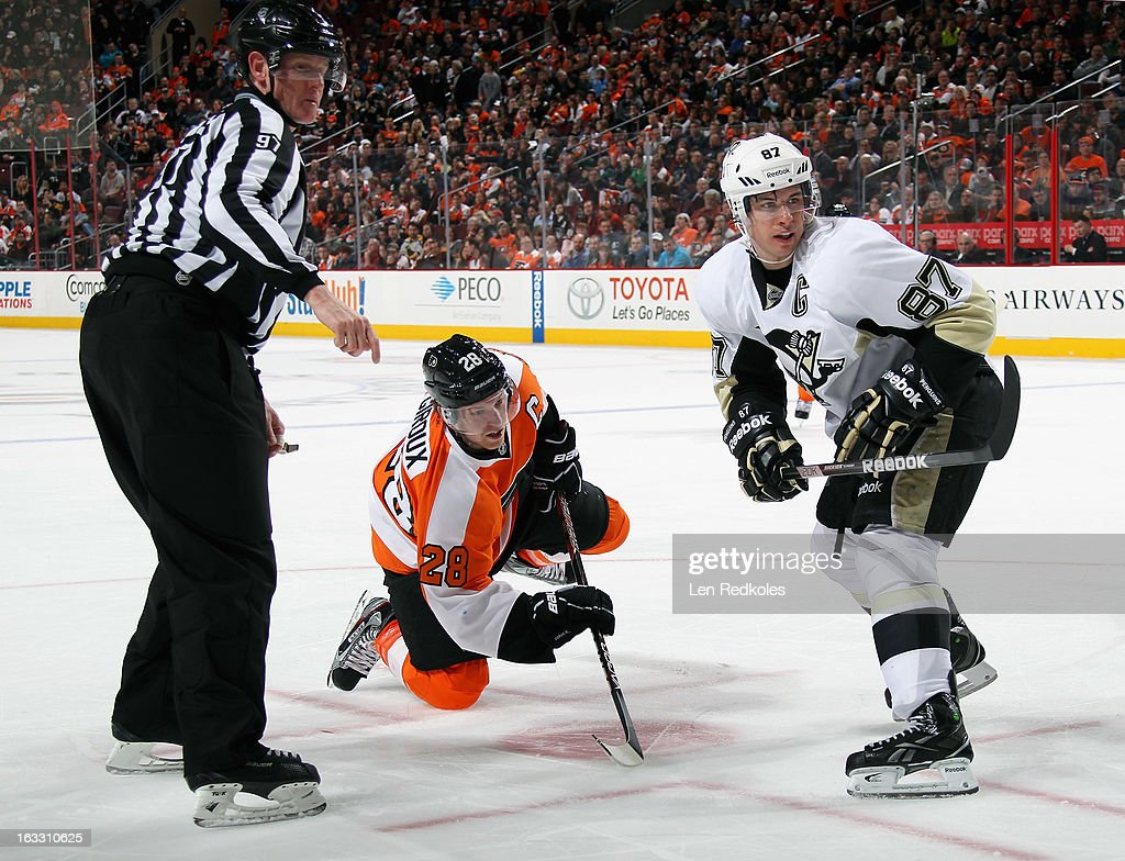 Claude Giroux #28 of the Philadelphia Flyers pushes the puck forward after a face-off against Sidney Crosby #87 of the Pittsburgh Penguins on March 7, 2013 at the Wells Fargo Center in Philadelphia, Pennsylvania. The Penguins went on to defeat the Flyers 5-4.