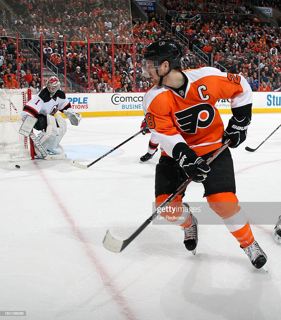 Claude Giroux #28 of the Philadelphia Flyers skates after the loose puck along side goaltender Johan Hedberg #1 of the New Jersey Devils on March 15, 2013 at the Wells Fargo Center in Philadelphia, Pennsylvania.
