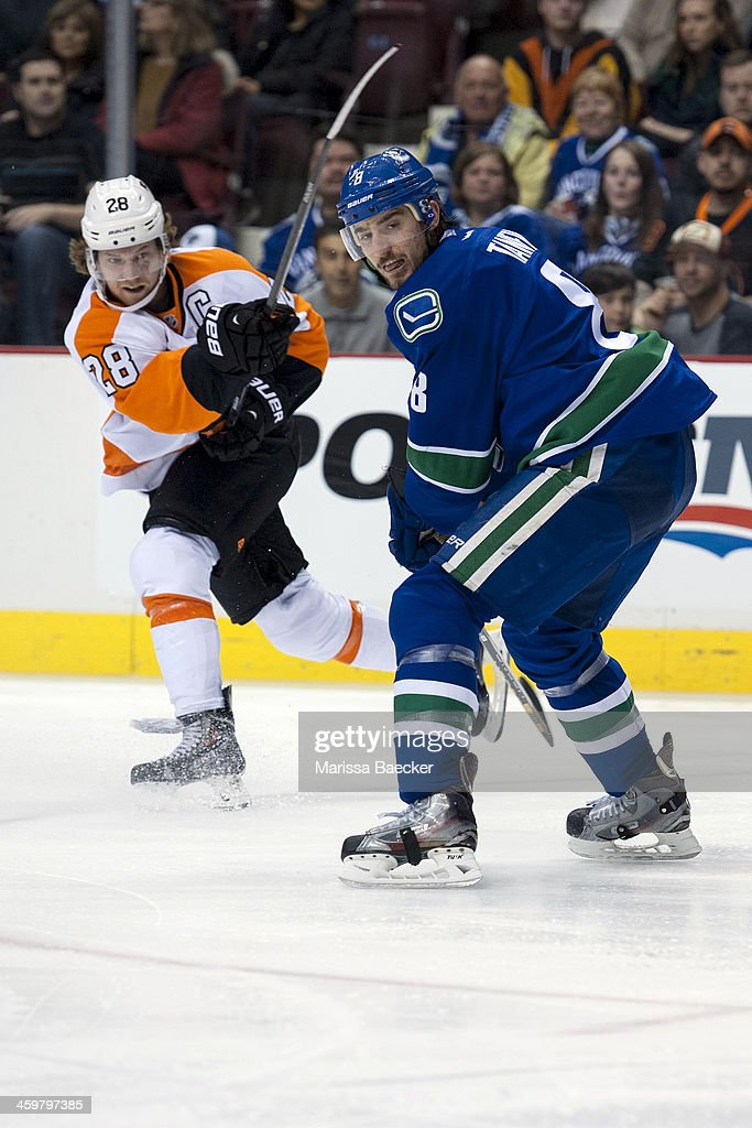 <a gi-track='captionPersonalityLinkClicked' href=/galleries/search?phrase=Claude+Giroux&family=editorial&specificpeople=537961 ng-click='$event.stopPropagation()'>Claude Giroux</a> #28 of the Philadelphia Flyers takes a shot while Chris Tanev #8 of the Vancouver Canucks checks on December 30, 2013 at Rogers Arena in Vancouver, British Columbia, Canada.
