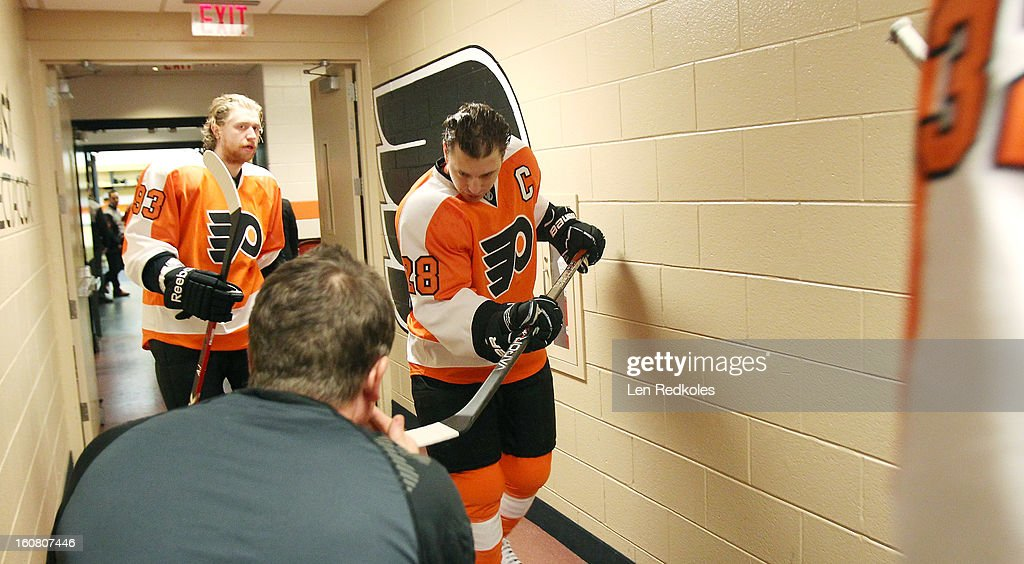 Claude Giroux #28 of the Philadelphia Flyers walks by equipment manager Derek Settlemyre as he prepares to enter the ice surface for warm-ups prior to his game against the Carolina Hurricanes on February 2, 2013 at the Wells Fargo Center in Philadelphia, Pennsylvania.
