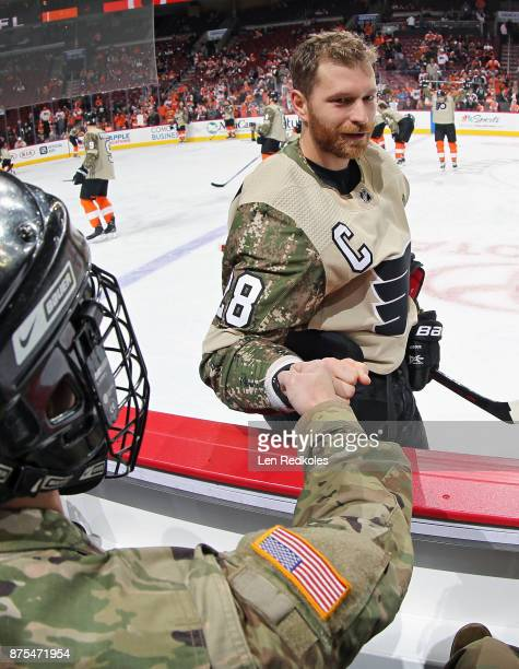 Claude Giroux of the Philadelphia Flyers wearing a camouflage jersey in honor of Military Appreciation night fist bumps a member of the military...