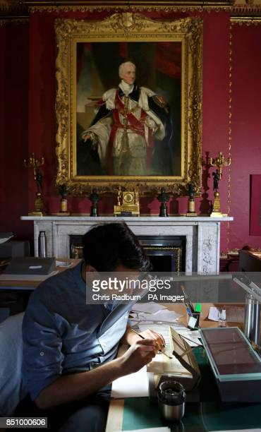 Claude GrewalSultze a Paper Conservator works on a collection of water stained books in the Red room at The National Trust's Wimpole Hall in...