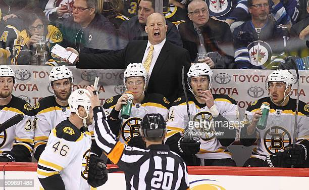 Claude Julien head coach of the Boston Bruins speaks to referee Tim Peel from the bench in third period action in an NHL game against the Winnipeg...
