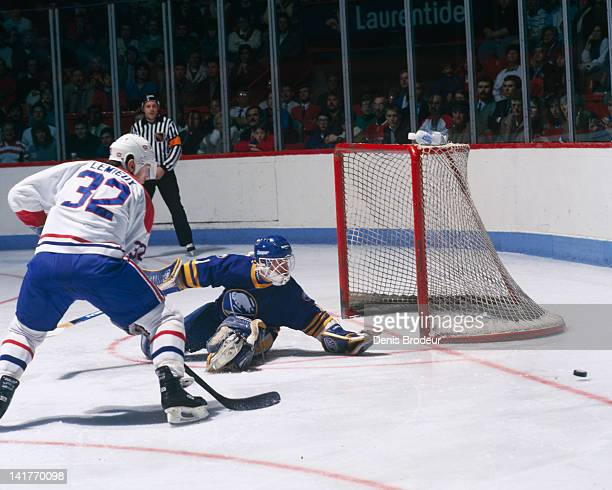 Claude Lemieux of the Montreal Canadiens and Jaques Cloutier of the Buffalo Sabres watch the puck as it slides past the net Circa 1980 at the...