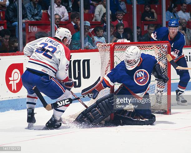 Claude Lemieux of the Montreal Canadiens attempts the slide the puck past the New York Islanders goalie Circa 1980 at the Montreal Forum in Montreal...