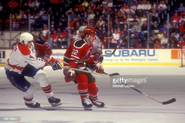 Claude Lemieux of the New Devils goes after a loose puck with pressure from Kevin Hatcher of the Washington Capitals during a hockey game on October...