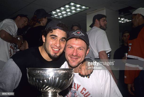 Claude Lemieux of the New Jersey Devils and Scott Gomez celebrate with the Stanley Cup Trophy after winning the 2000 Stanley Cup Finals game against...