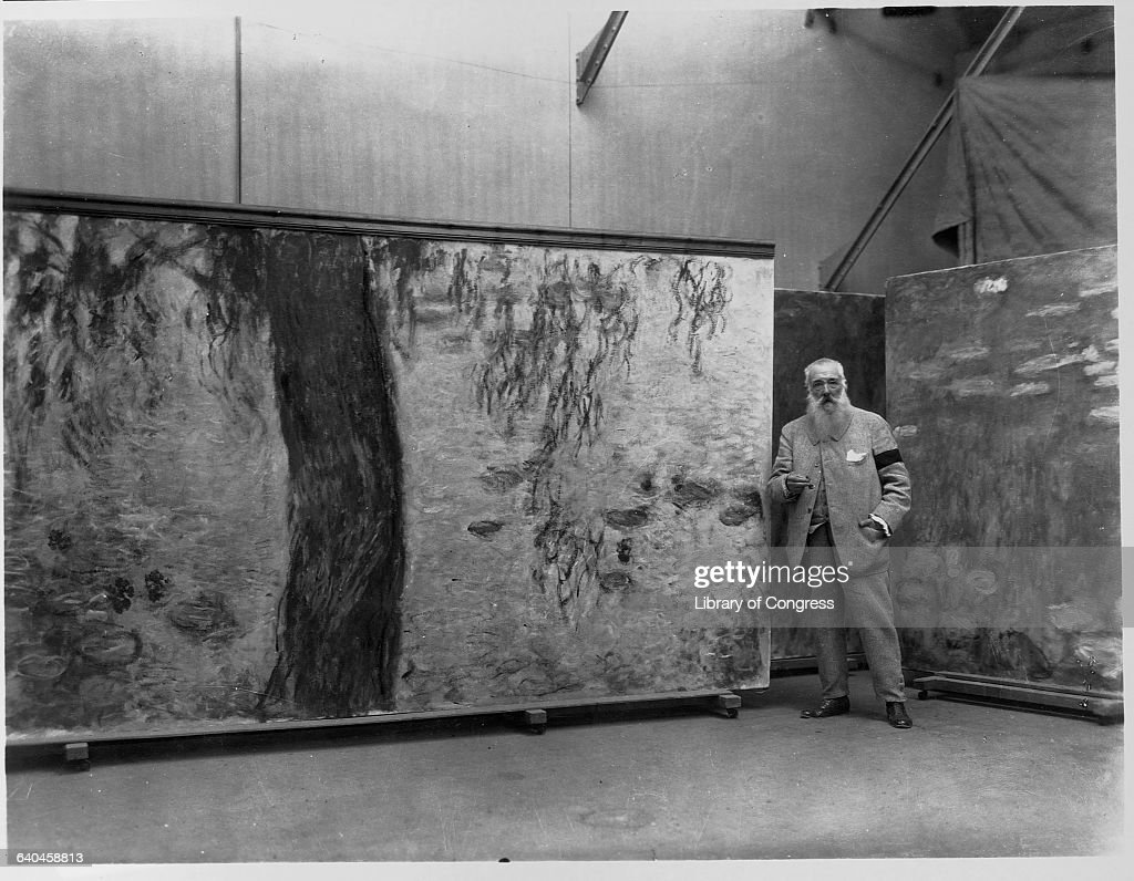 Claude Monet standing in his studio with a panel of his Nympheas mural. | Located in: Musee de l'Orangerie.