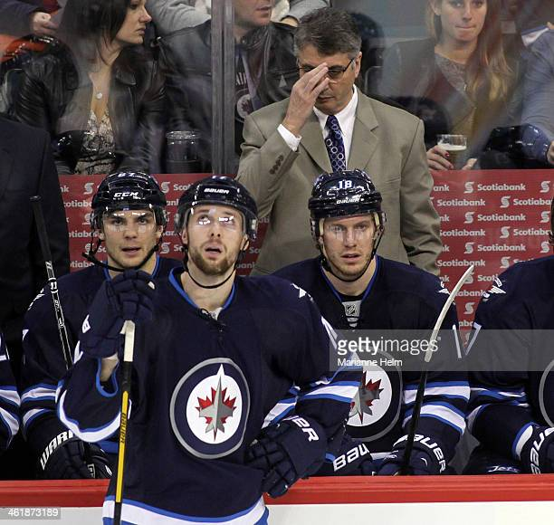 Claude Noel head coach of the Winnipeg Jets adjusts his glasses on the bench in third period action in an NHL game against the Columbus Blue Jackets...