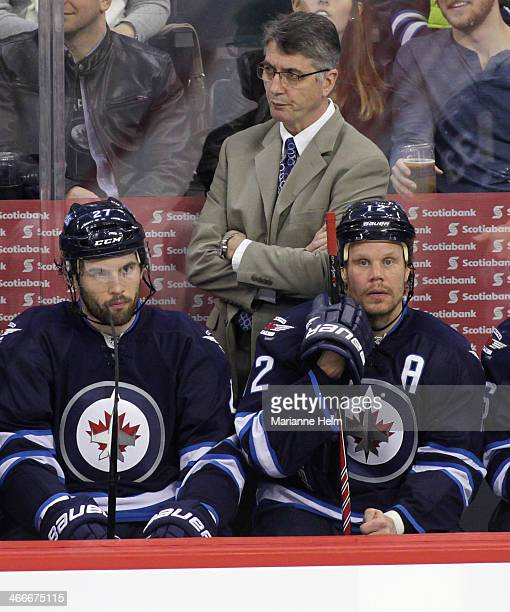 Claude Noel head coach of the Winnipeg Jets and players Eric Tangradi and Olli Jokinen watch from the bench during third period action in an NHL game...