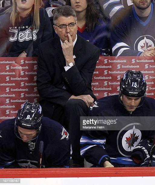 Claude Noel head coach of the Winnipeg Jets looks up at the replay during third period action in a game against the New York Islanders on April 20...
