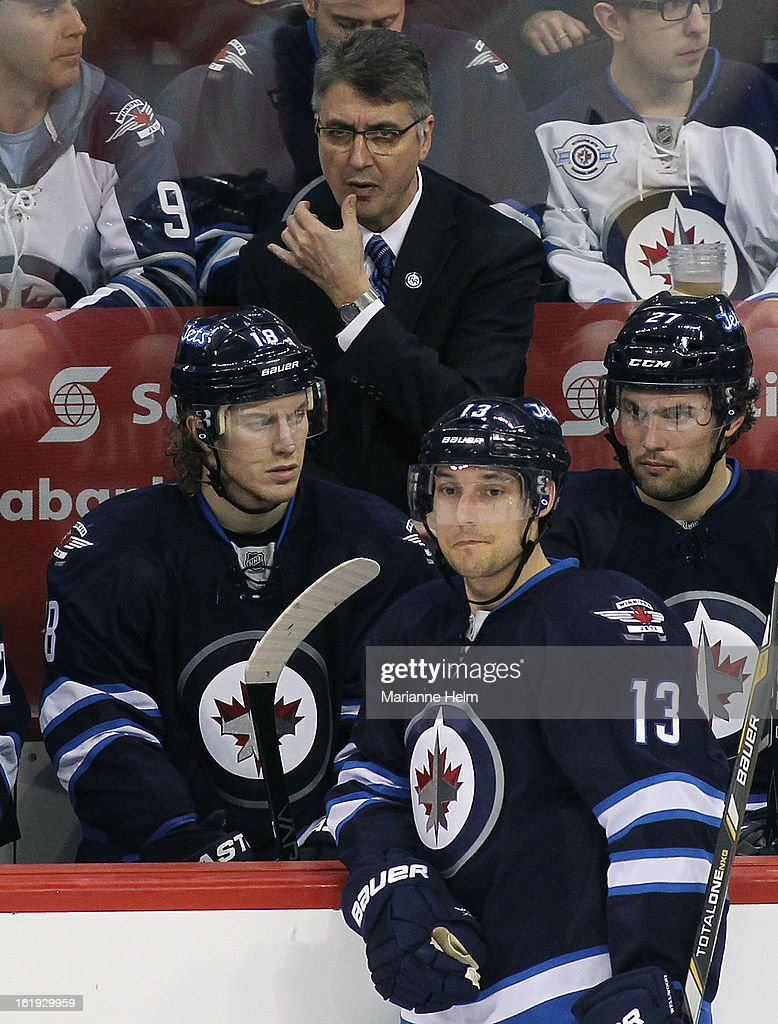 Claude Noel, head coach of the Winnipeg Jets, rubs his lip as <a gi-track='captionPersonalityLinkClicked' href=/galleries/search?phrase=Bryan+Little&family=editorial&specificpeople=540533 ng-click='$event.stopPropagation()'>Bryan Little</a> #18, <a gi-track='captionPersonalityLinkClicked' href=/galleries/search?phrase=Kyle+Wellwood&family=editorial&specificpeople=577984 ng-click='$event.stopPropagation()'>Kyle Wellwood</a> #13 and <a gi-track='captionPersonalityLinkClicked' href=/galleries/search?phrase=Eric+Tangradi&family=editorial&specificpeople=4361715 ng-click='$event.stopPropagation()'>Eric Tangradi</a> #27 wait at the bench during a break in play in a game against the Boston Bruins during third period action on February 17, 2013 at the MTS Centre in Winnipeg, Manitoba, Canada.
