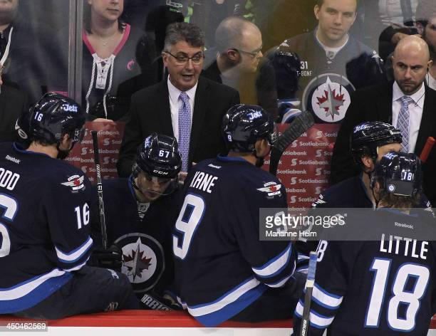 Claude Noel head coach of the Winnipeg Jets speaks to his players on the bench during a break in third period action in an NHL game against the...