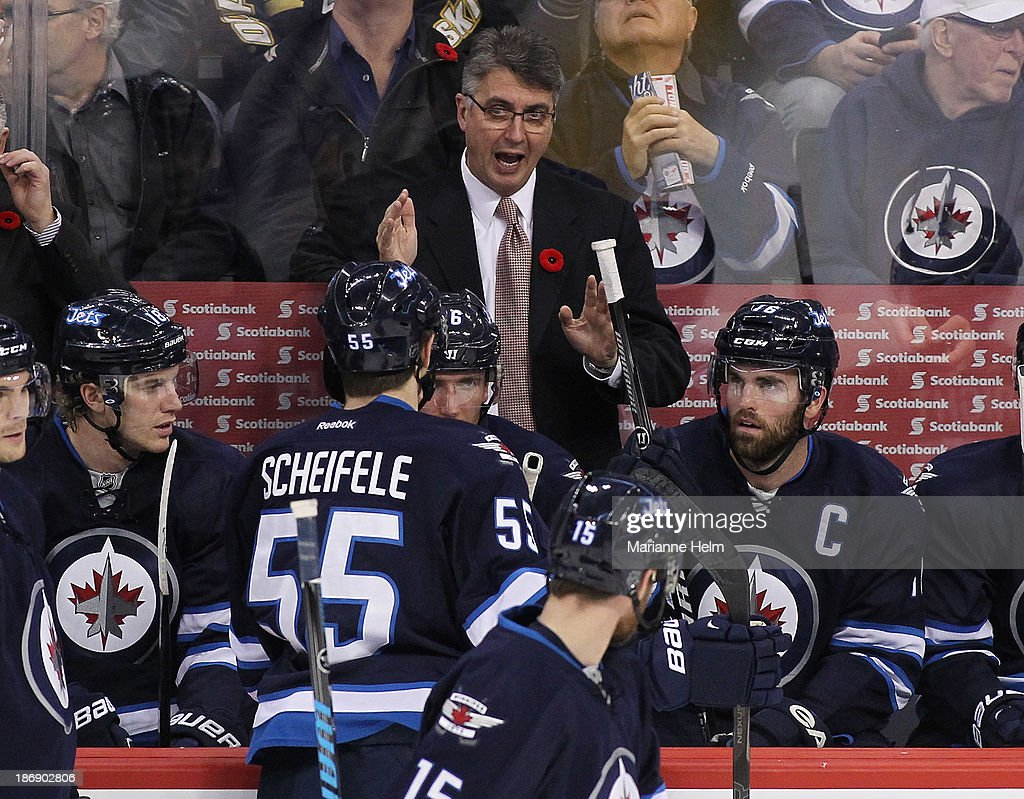 Claude Noel, head coach of the Winnipeg Jets, talks to his players on the bench during first period in an NHL game against the Detroit Red Wings at the MTS Centre on November 4, 2013 in Winnipeg, Manitoba, Canada.