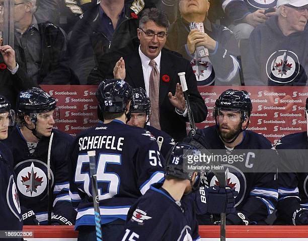 Claude Noel head coach of the Winnipeg Jets talks to his players on the bench during first period in an NHL game against the Detroit Red Wings at the...