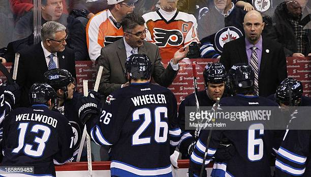 Claude Noel head coach of the Winnipeg Jets talks to his team during timeout from the bench during third period in a game between the Winnipeg Jets...