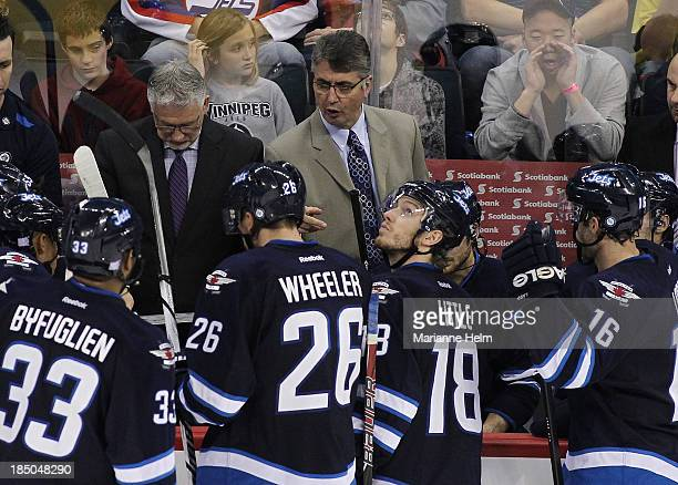Claude Noel head coach of the Winnipeg Jets talks to his team from the bench as Bryan Little looks up in third period action of an NHL game against...