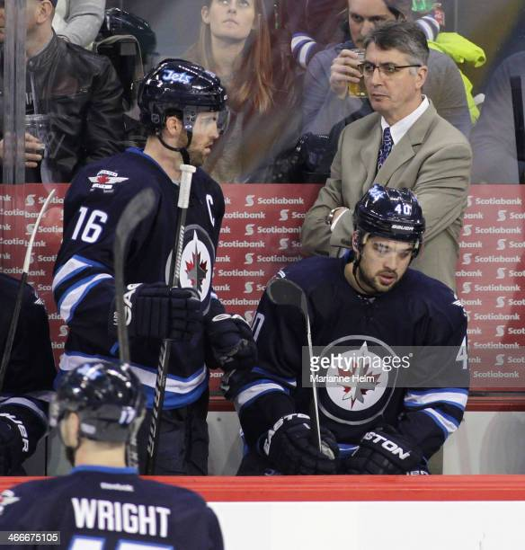 Claude Noel head coach of the Winnipeg Jets watches as captain Andrew Ladd makes his way to the bench during third period action in an NHL game...