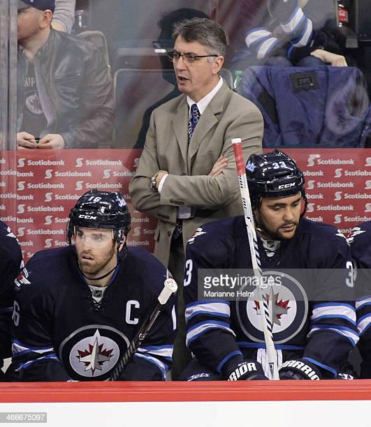Claude Noel head coach of the Winnipeg Jets watches from the bench as players Andrew Ladd and Dustin Byfuglien rest during third period action in an...