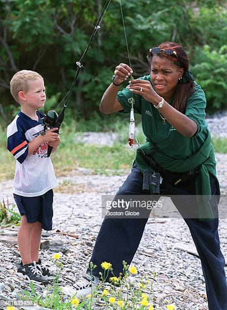 Claudette Bailey of Boston Parks and Recreation helps Kyle Briggs untangle his fishing line at the Long Island Fishing Derby The derby allowed...