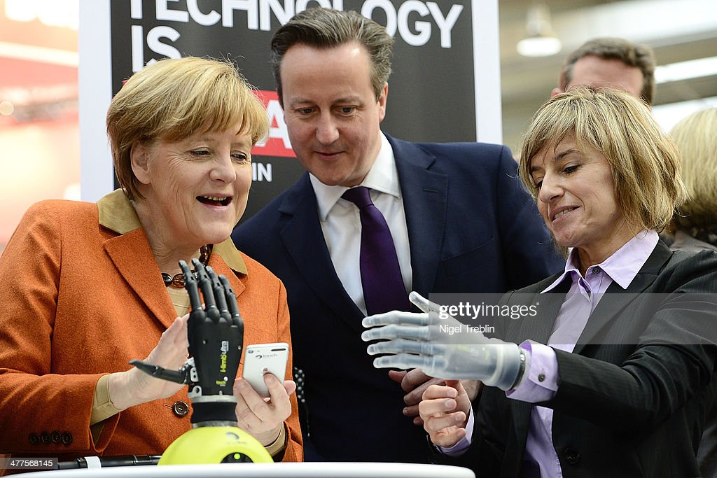 Claudia Breidbach (R) shows German Chancellor <a gi-track='captionPersonalityLinkClicked' href=/galleries/search?phrase=Angela+Merkel&family=editorial&specificpeople=202161 ng-click='$event.stopPropagation()'>Angela Merkel</a> and British Prime Minister David Cameron how to control her bionic hand I-Limb on the stand of Great Britain's Touch Bionic company the 2014 CeBIT technology Trade fair on March 10, 2014 in Hanover, Germany. CeBIT is the world's largest technology fair and this year's partner nation is Great Britain.