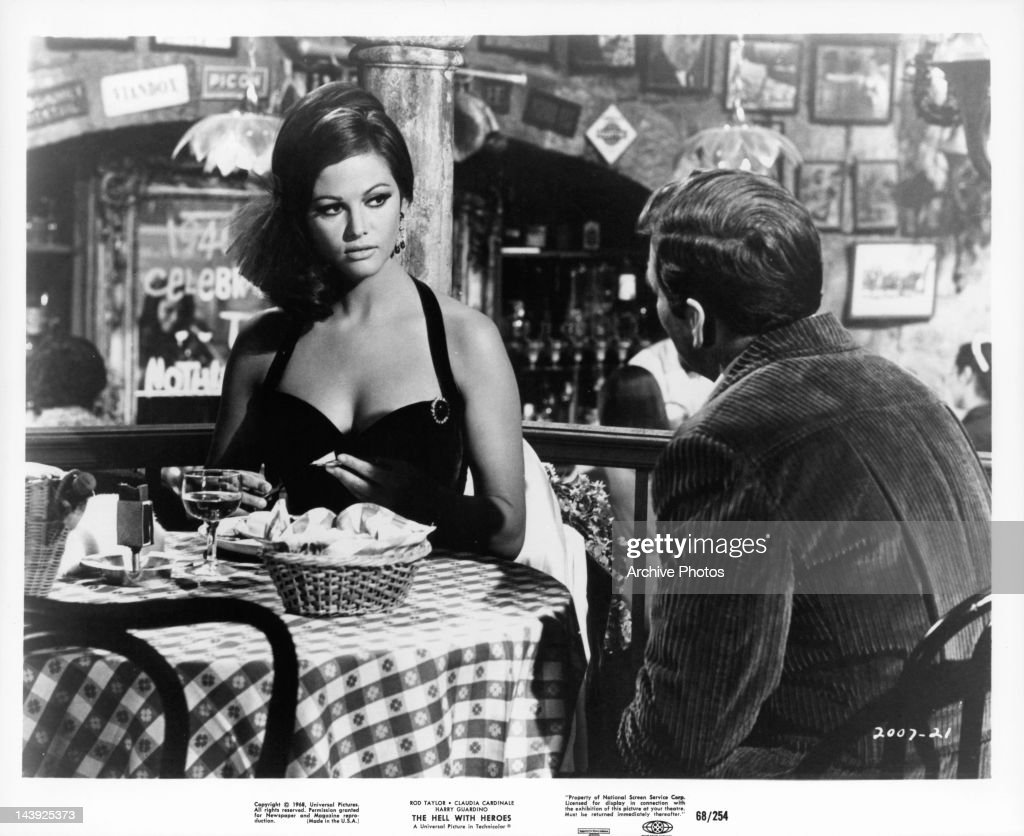 Claudia Cardinale at restaurant table with man in a scene from the film 'The Hell With Heroes', 1968.