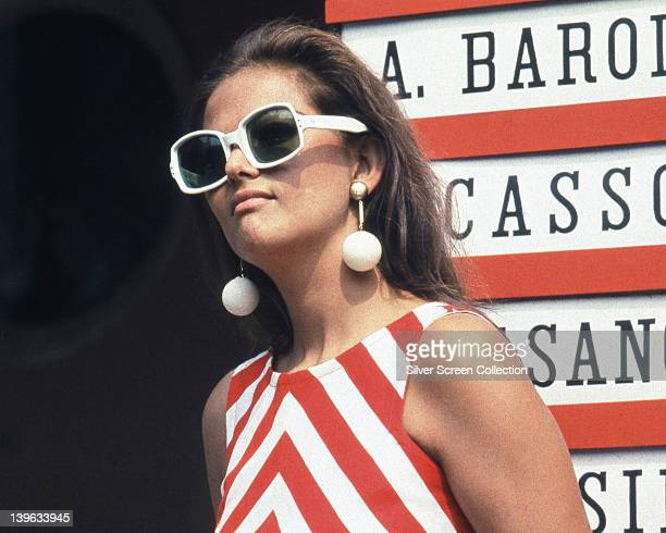 Claudia Cardinale Italian actress wearing a sleeveless red and white striped dress and sunglasses with white frames and white drop ball earrings...