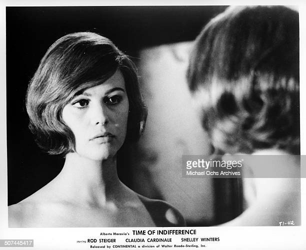 Claudia Cardinale looks in the mirror in a scene from the movie 'Time of Indifference' circa 1964