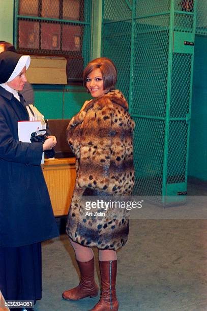 Claudia Cardinale wearing a fur coat talking to a woman dressed as a nun circa 1990 New York