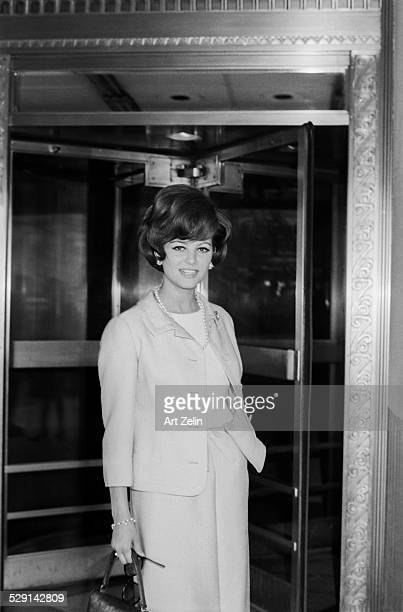 Claudia Cardinale wearing a pants suit in front of a revolving door circa 1970 New York