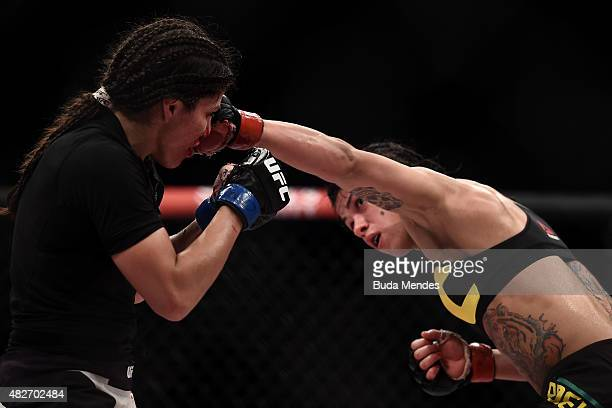 Claudia Gadelha of Brazil punches Jessica Aguilar of the United States in their strawweight bout during the UFC 190 Rousey v Correia at HSBC Arena on...