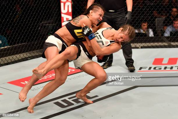Claudia Gadelha of Brazil takes down Karolina Kowalkiewicz of Poland in their womens strawweight bout during the UFC 212 event at Jeunesse Arena on...