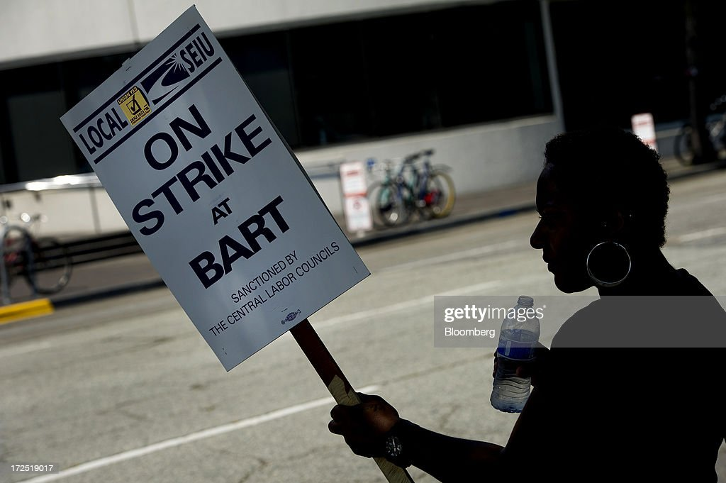 Claudia Horton, an administrative employee with the Bay Area Rapid Transit (BART) and a member of Service Employees International Union (SEIU) Local 1021, holds a sign as she joins other union members picketing in front of the Lake Merritt BART station in Oakland, California, U.S., on Tuesday, July 2, 2013. Trains linking downtown San Francisco to its airport and the East Bay area are likely to remain idle today, officials said, as a strike entered its second day, forcing about 400,000 riders to commute by car, bus or ferry. Photographer: David Paul Morris/Bloomberg via Getty Images