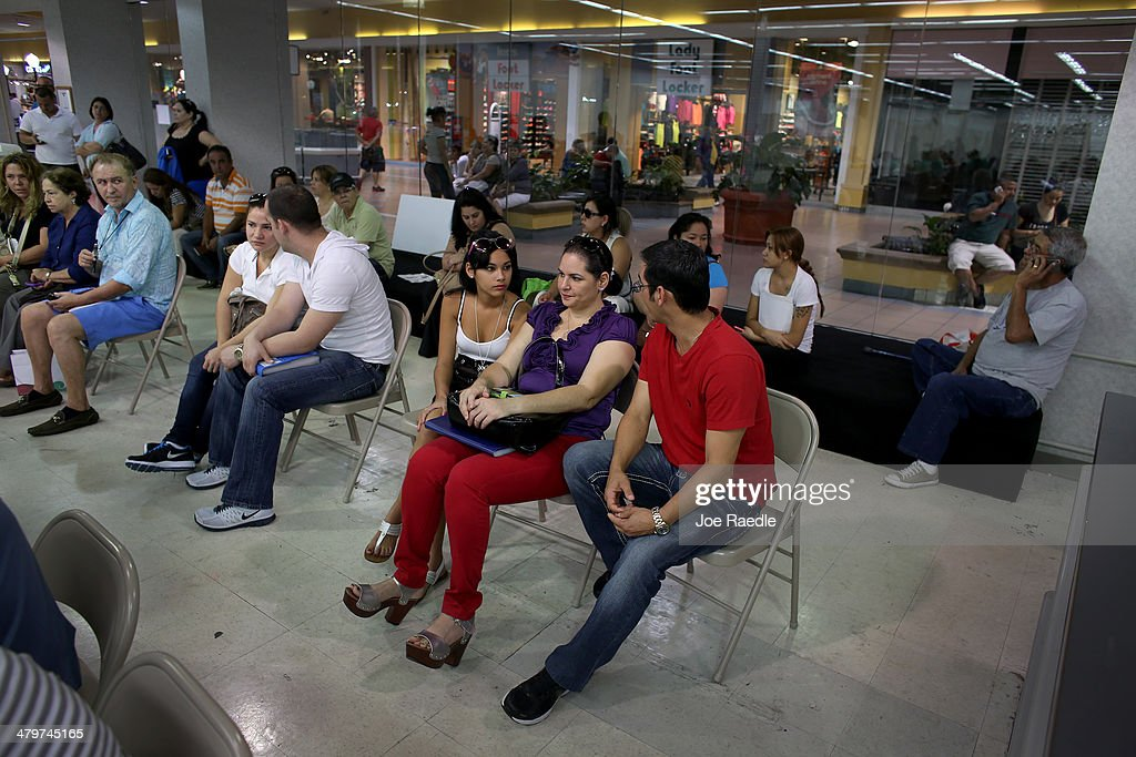 Claudia Suarez, Yudelmy Cataneda and Javier Suarez wait for their name to be called to speak with an insurance agent from Sunshine Life and Health Advisors as they and others try to purchase health insurance under the Affordable Care Act at a store setup in the Mall of Americas on March 20, 2014 in Miami, Florida. The owner of Sunshine Life and Health Advisors, Odalys Arevalo, said she has seen a surge in people, some waiting up to 3 hours or more in line, trying to sign up for the Affordable Care Act before the open enrollment period for individual insurance ends on March 31.