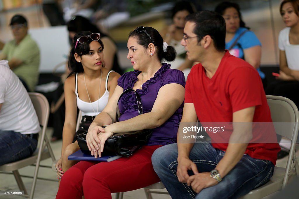 Claudia Suarez, Yudelmy Cataneda and Javier Suarez (L-R) wait for their names to be called to speak with an insurance agent from Sunshine Life and Health Advisors as they and others try to purchase health insurance under the Affordable Care Act at a store setup in the Mall of Americas on March 20, 2014 in Miami, Florida. The owner of Sunshine Life and Health Advisors, Odalys Arevalo, said she has seen a surge in people, some waiting up to 3 hours or more in line, trying to sign up for the Affordable Care Act before the open enrollment period for individual insurance ends on March 31.