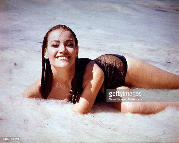 Claudine Auger French actress wearing a brown swimsuit posing in the surf in a publicity portrait issued for the film 'Thunderball' 1965 The James...
