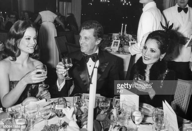 Claudine Auger Robert Stack et Dewi Sukarno lors d'une dîner au Pré Catelan le 5 décembre 1971 à Paris France