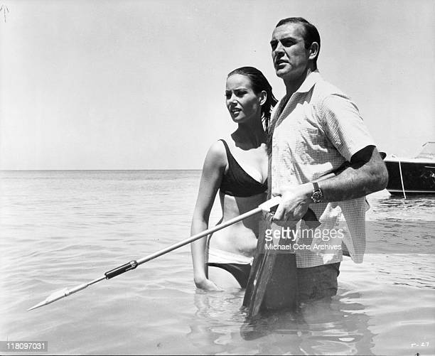 Claudine Auger standing with Sean Connery in the water in a scene from the film 'Thunderball' 1965