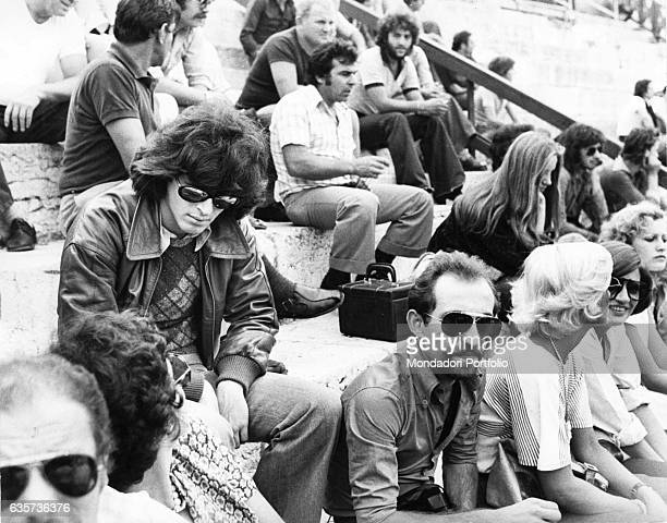 Claudio Baglioni the Italian singersongwriter sitting on the bleachers of an amphitheater Italy 1975